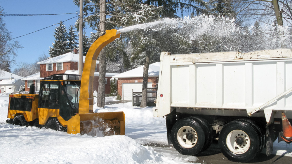 trackless vehicles twin auger snowblower on sidewalk tractor in snow with truck loading chute