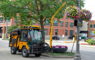 trackless vehicles watering arm attachment on sidewalk municipal tractor with water tank side view
